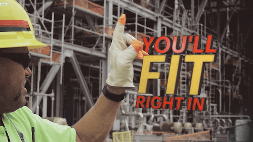 A construction man signals to someone on his construction site