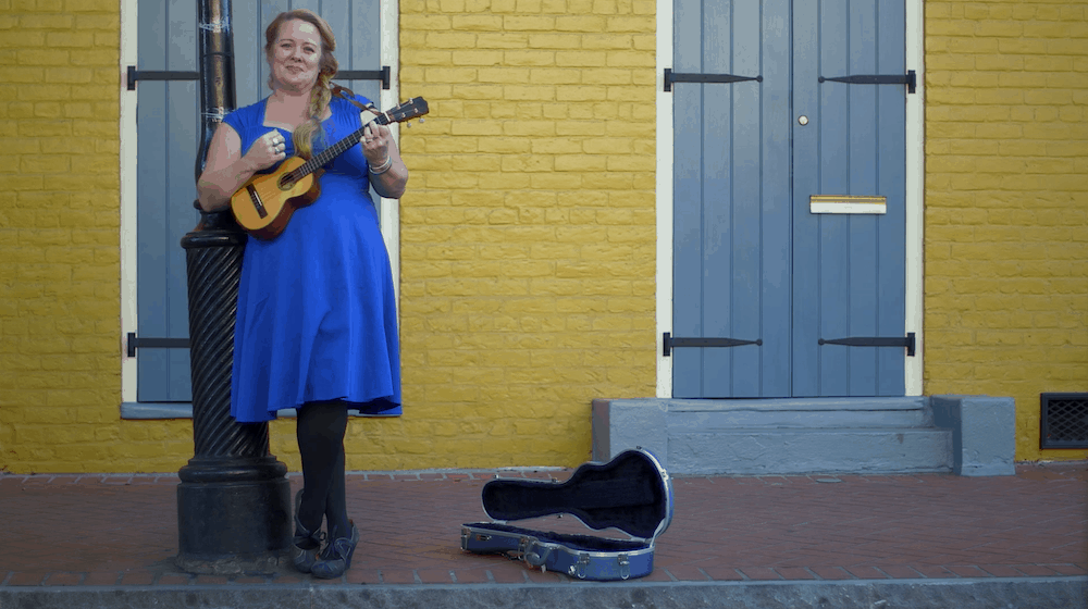 A street musician plays a ukulele in front of a yellow brick wall